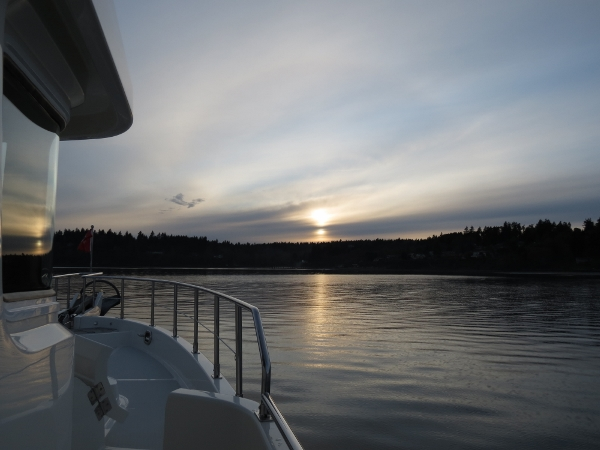 Sunset reflected in the pilothouse window as we approach the anchorage at Tramp Harbor.